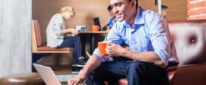 Man working on a leather couch on his laptop drinking coffee